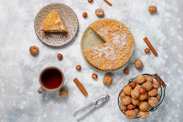 Ciasto marchewkowe ze 2020 świecami i filiżanką herbaty na szarym betonie