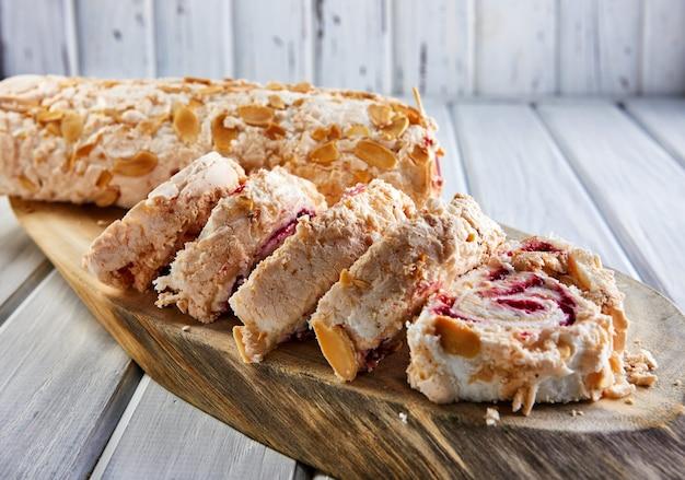 Ciasto merengue z pistacjami i dżemem na drewnianej desce.