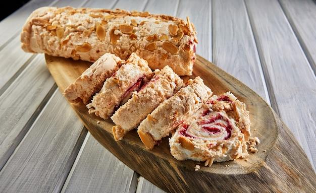 Ciasto merengue z pistacjami i dżemem na drewnianej desce