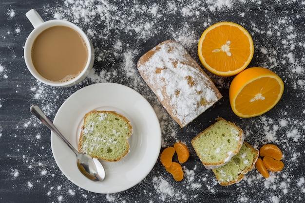 Ciasto miętowe na ciemnej powierzchni ze świeżymi pomarańczowymi mandarynkami.