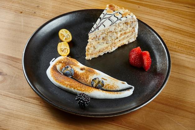Ciasto miód z warstwami i kremem cukierniczym na powierzchni drewnianych. kawałek pysznego ciasta medovik. ścieśniać. koncepcja smaczne piekarni. selektywne ustawianie ostrości