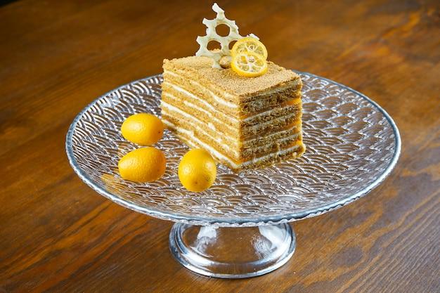 Ciasto miód z warstwami i kremem cukierniczym na przezroczystym talerzu na drewnianym stole. kawałek pysznego ciasta medovik. ścieśniać. koncepcja smaczne piekarni.