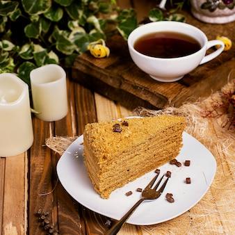 Ciasto miodowe, kawałek medovik z filiżanką herbaty.