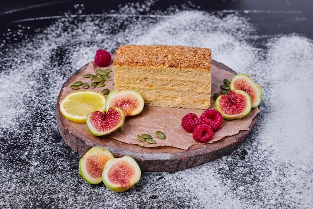 Ciasto miodowe ozdobione figami, jagodami i plasterkiem cytryny pośrodku ciemnego stołu.