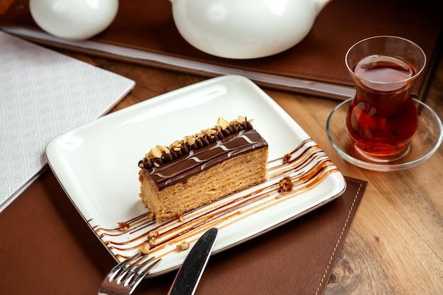 Ciasto miodowe przekładane warstwami ciasta z czekoladowymi orzechami i stołem z czarnym teonem