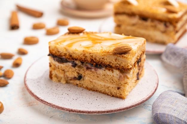 Ciasto miodowe z kremem mlecznym, karmelem, migdałami i filiżanką kawy na białym betonowym tle i lnianą tkaniną.