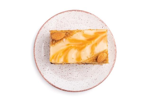 Ciasto miodowe z kremem mlecznym, karmelem, migdałami na białym tle na białej powierzchni