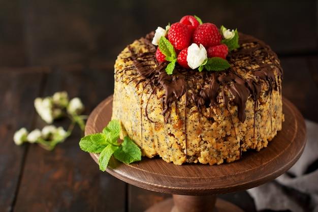 Ciasto mrowisko ozdobione malinami, czekoladą i orzechami na starym drewnianym stole. selektywna ostrość.