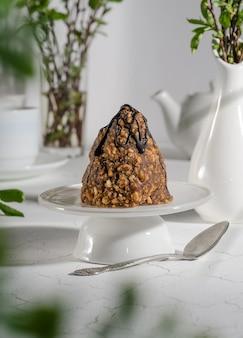 Ciasto mrowisko ze skondensowanym mlekiem, polane czekoladą na białej podstawce i liście na pierwszym planie