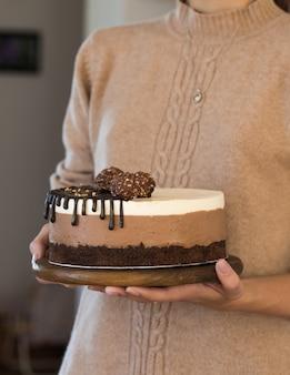 """Ciasto musowe """"trzy czekoladowe"""". kawałek ciasta wykonany z trzech warstw czekolady o różnych kolorach suflet w ręce kobiety"""