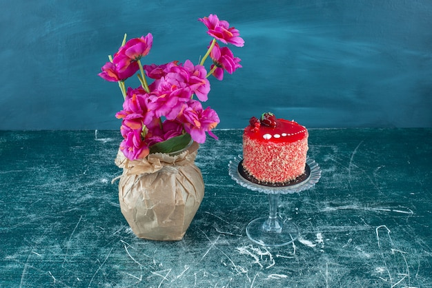 Ciasto na cokole obok wazonu z kwiatami na niebiesko.