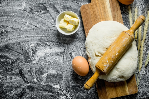 Ciasto na desce do krojenia z wałkiem do ciasta. na rustykalnym stole