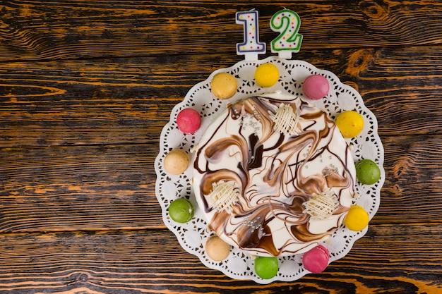 Ciasto na nowy rok i święta na drewnianym tle, w pobliżu świec numer 12, koncepcja nowego roku