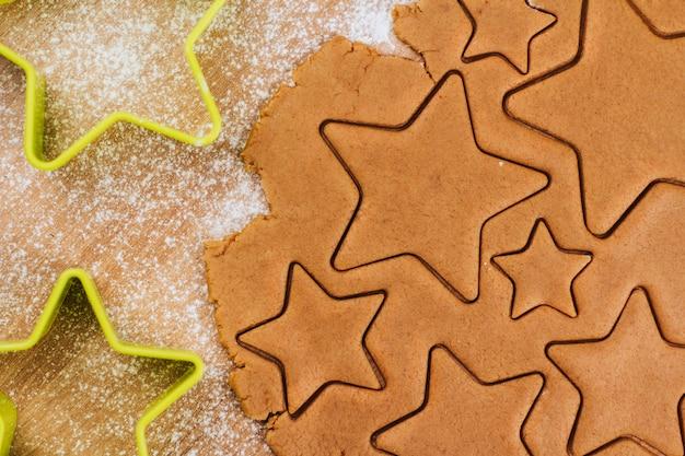 Ciasto na pierniki na stole posypanym mąką. cięcie ciasteczek w kształcie gwiazdek.