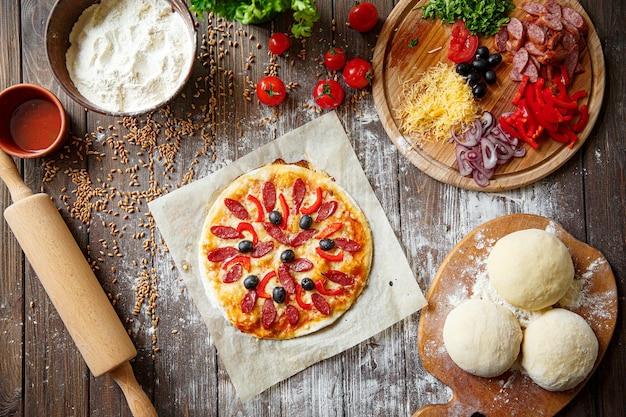Ciasto na pizzę z dodatkami na drewnie