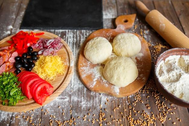 Ciasto na pizzę ze składnikami na stół z drewna
