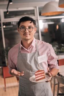 Ciasto na talerzu. młody inteligentny obiecujący przedsiębiorca trzyma pyszne ciasto na białym talerzu tworzą swoją kawiarnię