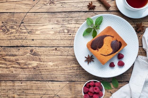 Ciasto na talerzu z czekoladowymi ciasteczkami i twarogiem z malinami