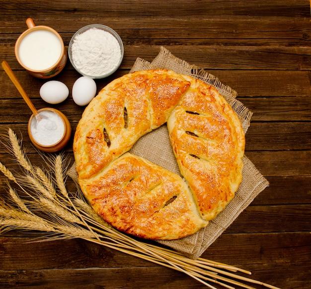 Ciasto na zwolnieniu, składniki do pieczenia, kłosy pszenicy i kubek mleka na drewnianym.