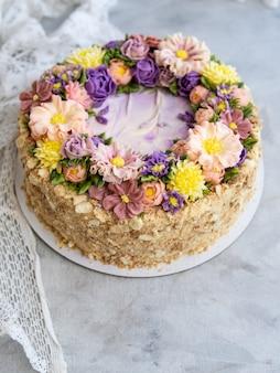 Ciasto napoleon z kremem waniliowym, ozdobione kwiatami maślanki