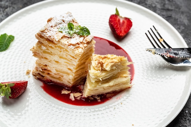 Ciasto napoleona. przepiękny tort z kremem waniliowym z kremem, jabłkami i konfiturą truskawkową ozdobiony miętą
