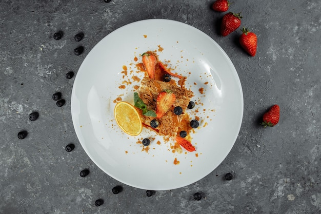 Ciasto napoleona z sosem karmelowym. delikatne ciasto francuskie z sosem budyniowo-karmelowym ozdobione truskawkami, jagodami i miętą.