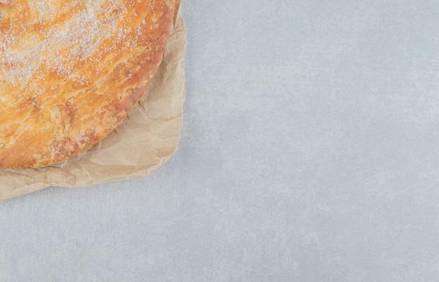Ciasto okrągłe ozdobione białym proszkiem na arkuszu.