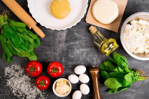 Ciasto, olej, ser, pomidory, jajka, warzywa na szarej drewnianej powierzchni