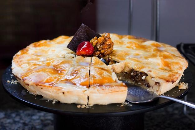 Ciasto orzechowe z malinami, ozdobione świeżymi truskawkami, na czarnym tle