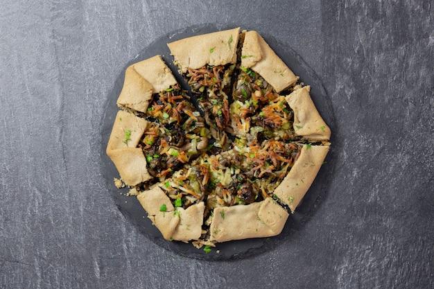 Ciasto otwarte, galette, z pieczarkami, smażoną zieloną cebulą, świeżymi ziołami i nadzieniem serowym na ciemnym tle.