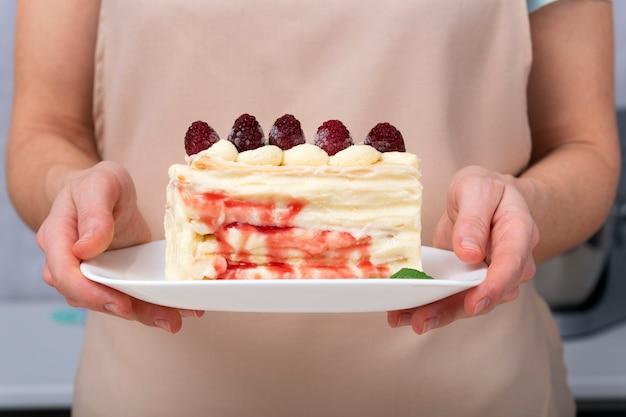 Ciasto owocowe na spodku w rękach kobiet. ścieśniać. kawałek ciasta z jagodami i śmietaną.