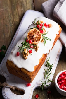 Ciasto owocowe posypane lukrem, orzechami, pestkami granatu i suchym pomarańczowym zbliżeniem. świąteczne i zimowe wakacje domowe ciasto