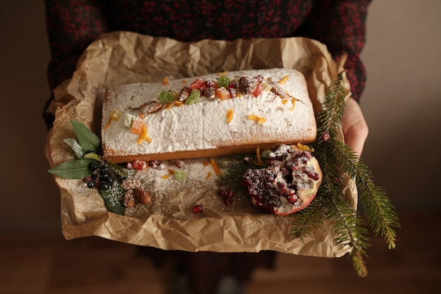 Ciasto owocowe posypane pokrojonymi w kostkę lukrem, orzechami, pestkami granatu i suchym pomarańczowym zbliżeniem. świąteczne i zimowe wakacje domowe ciasto