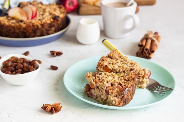 Ciasto owsiane lub pieczone płatki owsiane z jabłkami i rodzynkami. dietetyczne jesienne śniadanie.