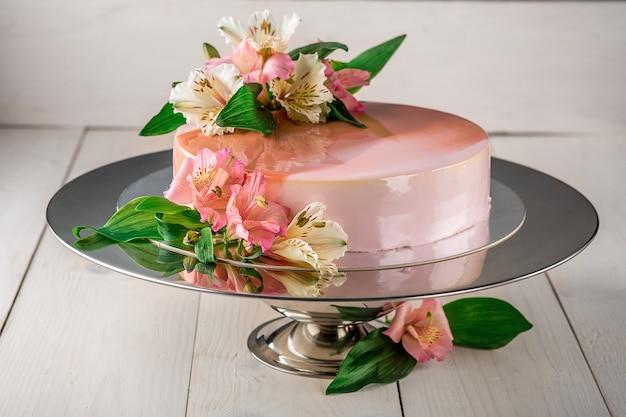 Ciasto ozdobione kwiatami. tort weselny na stojaku na białym drewnianym tle