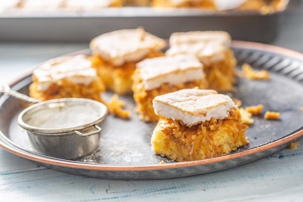 Ciasto pokrojone w kostkę na starej tacy z sitkiem do cukru i blachą do pieczenia w tle.