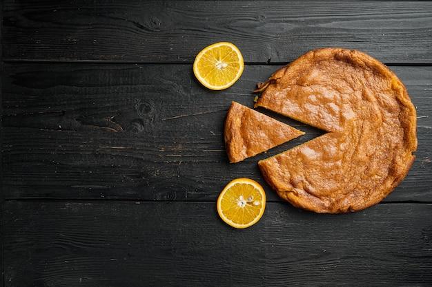 Ciasto pomarańczowe i mandarynki z zestawem polenty, na czarnym tle drewnianego stołu, widok z góry płasko leżący, z miejscem na kopię na tekst