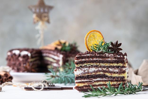 Ciasto przekładane czekoladą udekorowane rozmarynem i suszonymi plasterkami pomarańczy