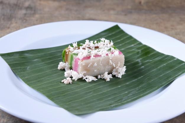 Ciasto przekładane i wiórki kokosowe na talerzu z liściem bananowca, jedzenie malajskie