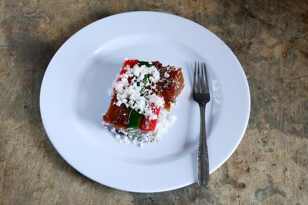Ciasto przekładane i wiórki kokosowe na talerzu ze sztućcami, jedzenie malajskie