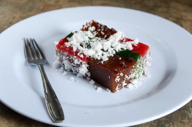 Ciasto Przekładane I Wiórki Kokosowe Na Talerzu Ze Sztućcami, Jedzenie Malajskie Premium Zdjęcia