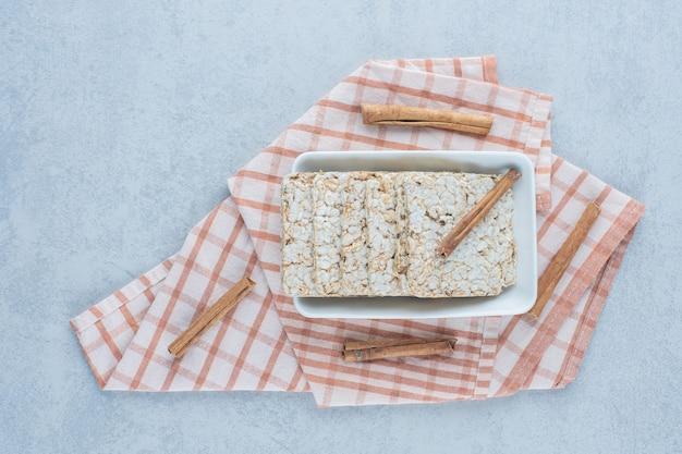 Ciasto ryżowe dmuchane i laski cynamonu w misce na ręczniku na marmurze.
