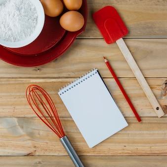 Ciasto składniki na talerzu z naczyniami i ślimakowatym notepad na drewnianej powierzchni