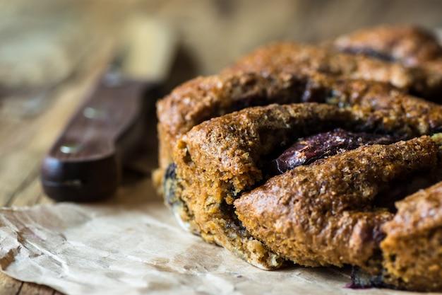 Ciasto śliwkowe wegańskie bezglutenowe, nóż, drewniany stół kuchenny, rustykalny styl kinfolk