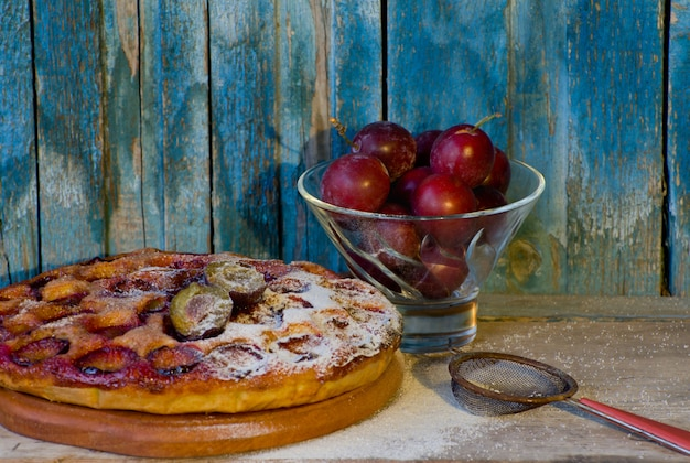 Ciasto śliwkowe z cukrem pudrem, sitko, piala ze śliwkami
