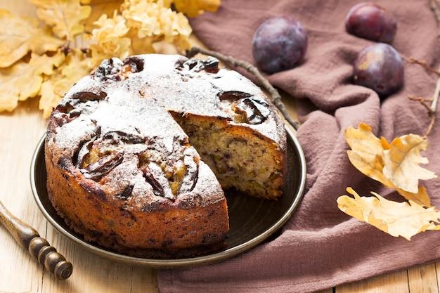 Ciasto śliwkowe z orzechami i czekoladą na podłoże drewniane. styl rustykalny, selektywna ostrość.