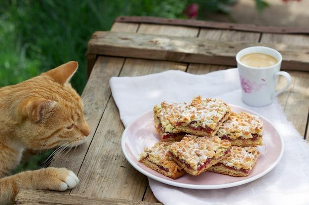 Ciasto streusel nadziewane konfiturą różaną, podawane z kawą. styl rustykalny.