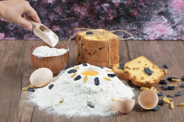 Ciasto sultana z składnikami na drewnianym pokładzie.