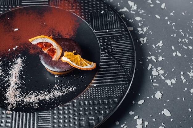 Ciasto. surowy wegetariański deser z suszonych owoców, orzechów i kremowej kompozycji nerkowca, masła kokosowego, chleba świętojańskiego. na talerzu, odizolowywającym na czarnym tle, zamyka up