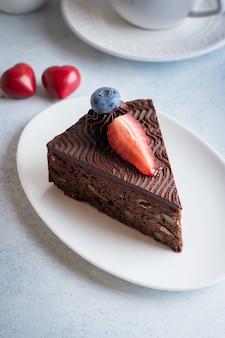 Ciasto świąteczne na deser. pyszny kawałek ciasta czekoladowego z filiżanką kawy i mlekiem na niebieskim kamiennym stole betonowym. koncepcja żywności śniadanie. świąteczne dekoracje świąteczne